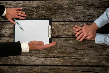 Obenliegende Ansicht des Geschäfts Arbeitgeber Mitarbeiter am Schreibtisch sitzen Verhandlungen über Arbeitsbedingungen, wie der Arbeitgeber seine Hand in Handshake bietet, konzentrieren sich auf die Hand mit einem Handschlag.