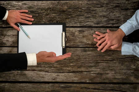 negotiation business: Overhead view of business employer an employee sitting at office desk negotiating about employment conditions as the employer offers his hand in handshake, focus to the hand offering a handshake. Stock Photo