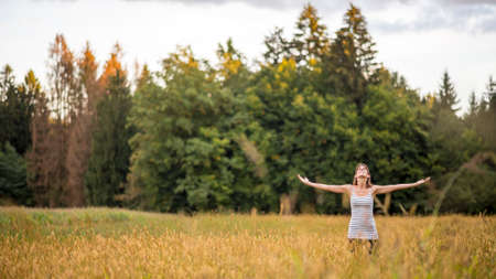 Young woman standing in the middle of autumn meadow with high golden grass looking up towards the sky with her arms spread widely as she enjoys fresh air and beauty of nature. Stock Photo