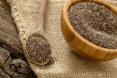 burlap sac: Wooden spoon and bowl full of healthy nutritious chia seeds lying on a burlap sac.