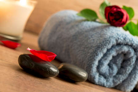 spoiling: Romantic atmosphere with a red rose on top of rolled towel, lit candle and black massage stones decorated with rose petals.