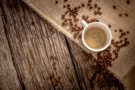 burlap sac: Top view of freshly brewed cup of delicious coffee on a burlap sac over rustic textured wooden boards with coffee beans scattered all around with blank space on the left side ready for your text.