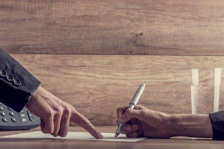 contrato de trabajo: Primer plano de empresario mostrando su empleado dónde firmar un contrato, con un efecto de filtro retro.