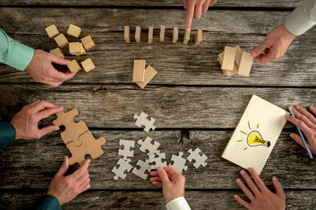 challenging: Businessmen planning business strategy while holding puzzle pieces, creating ideas with light bulb drawn on paper and rearranging wooden blocks. Conceptual of teamwork, strategy, vision or education.