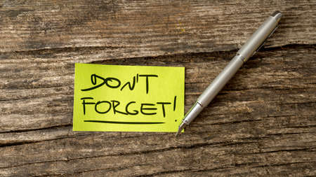 emphasized: Overhead view of a Dont forget reminder message written on green piece of paper lying on a textured wooden desk next to a silver pen.