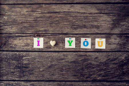i love you sign: I love you sign assembled of coloured letters and heart made of marble over a textured rustic background. Conceptual of love, relationship and romance, with a retro filter effect. Stock Photo