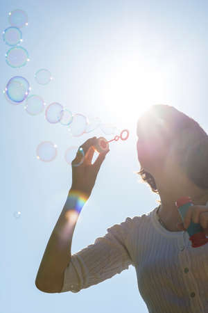 playfulness: Young woman blowing soap bubbles against a clear blue sky in a moment of purity and playfulness. Stock Photo