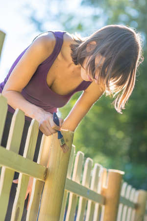 impacts: Young woman varnishing a wooden fence outdoors in her backyard to protect it from weather impacts and time. Stock Photo