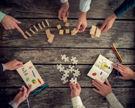 challenging: Businesspeople organizing business strategy while holding puzzle pieces, writing down ideas on paper and rearranging wooden blocks. Concept of brainstorming, management, innovation or creativity.