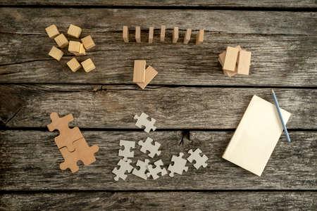 Vista dall'alto della scrivania di legno pronto per uno studente o un ingegnere per iniziare a lavorare, la creazione di idee ed esplorare - vuoto blocco note, matita e pile di pezzi di un puzzle, blocchi di legno e chiodi che si trovano sulla scrivania.