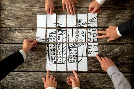 Draufsicht von acht Architekten oder Stadtplaner in der Stadtentwicklung und Nutzung von Land kooperierende mit der Hand gezeichnete Bild von hohen Gebäuden auf weißen Karten zusammenbauen. Lizenzfreie Bilder