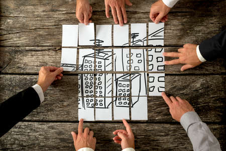 Top view of eight architects or urban planners cooperating in urban development and use of land by assembling hand drawn image of high buildings on white cards. Stock Photo