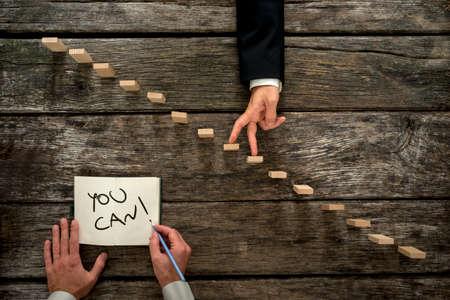 Conceptueel beeld van persoonlijke groei en loopbaanontwikkeling met zakenman zijn vingers lopen op houten stappen, terwijl zijn collega of mentor hem aanmoedigt met een U kunt bericht.