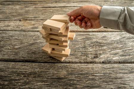 Mano maschio che la creazione o la costruzione di una torre di molti blocchi di legno su una texture scrivania rustico. Concettuale di istruzione, sviluppo di carriera e la visione di business o di start up.