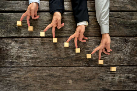 success strategy: Conceptual image of teamwork and cooperation - four male hands walking their fingers up towards promotion and success on wooden blocks in the form of a staircase. Stock Photo