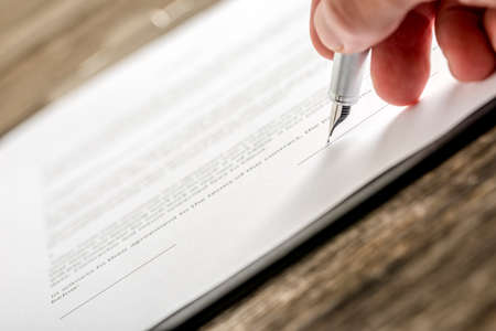 Man signing business document, application, subscription form  or insurance papers with silver pen on wooden desk. Imagens