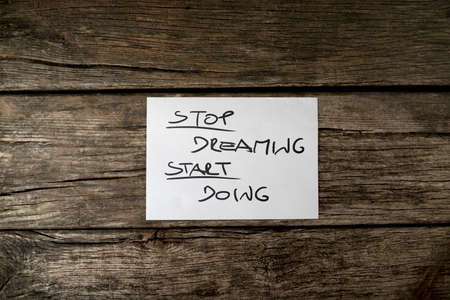 card stop: Top view of a Stop dreaming start doing message written on a white card lying on wooden rustic desk.