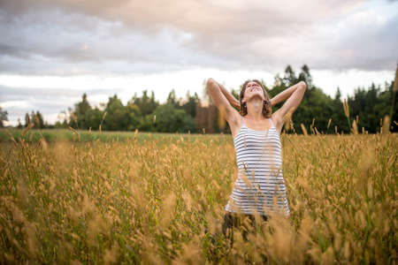 Young woman standing in the middle of autumn meadow with high golden grass holding her arms behind her head as she looks up in the glorious sky enjoying a peaceful energetic moment.
