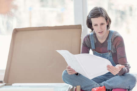 homey: Young woman sitting on the floor of her new home next to a cardbox with new furniture as she reads the instruction manual in a DIY and renovation concept.