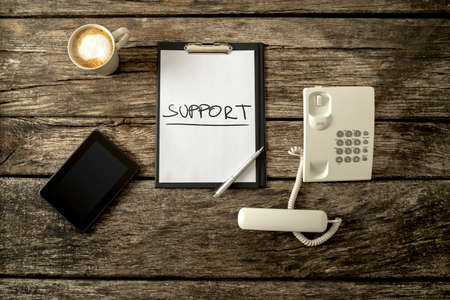 problem: Customer service and support concept - top view of a rustic wooden office desk prepared for work with a white telephone, digital tablet, white sheet of paper with Support sign and a cup of coffee. Stock Photo