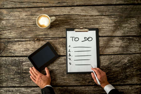 papel de notas: Top view of male hand writing a To do list on a white sheet of paper with digital tablet and cup of coffee alongside on his textured rustic wooden desk.