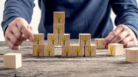Front view of a man arranging wooden blocks with hand drawn yellow lightbulb in a random structure. Conceptual of research, education and innovation. Archivio Fotografico