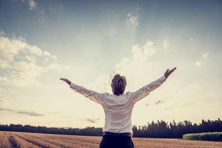 Retro immagine di uomo d'affari vittorioso giovane celebra il suo successo e il raggiungimento da piedi sotto cielo maestoso alzando le braccia in segno di gratitudine e soddisfazione.