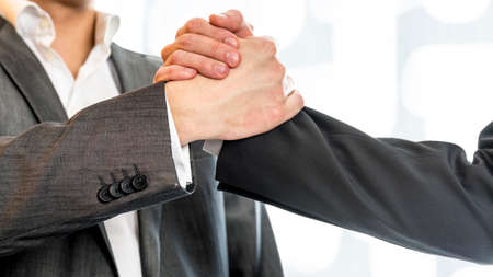 griping: Close up of two businessmen in gray business suit gripping their hands in success and agreement at the office.