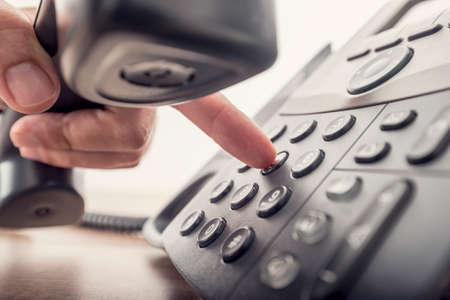 llamando: Primer de la mano masculina la celebración de auricular del teléfono al marcar un número de teléfono para realizar una llamada con un teléfono fijo negro. Con efectos retro filtro. Foto de archivo