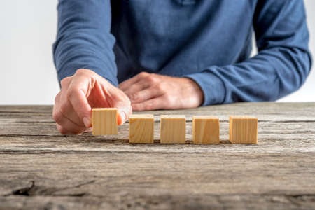 placing: Front view of a man placing five wooden cubes on a textured wooden desk. Stock Photo