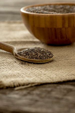 sac: Wooden spoon full of chia seeds lying on burlap sac with a wooden bowl in background. Stock Photo