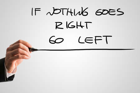 idealism: Male hand writing an If nothing goes right go left message from behind a grey virtual screen. Stock Photo