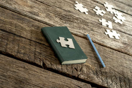 fundamental: Conceptual image of knowledge, wisdom and research - a piece of puzzle lying on a closed notebook with a pencil and other puzzle pieces lying alongside on a textured wooden desk. Stock Photo