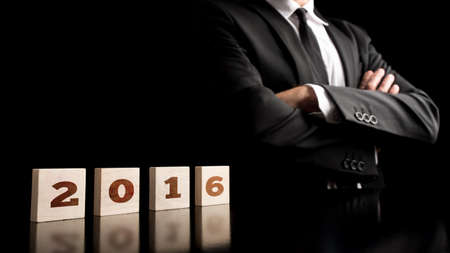 new direction: Business vision for the coming year 2016  - 2016 sign spelled over wooden cubes with businessman confidently standing next to it, over black background.