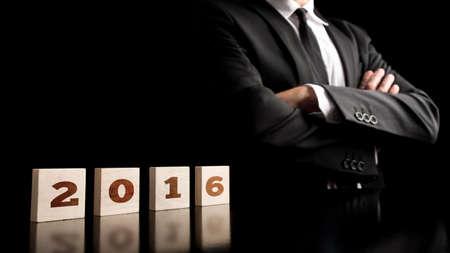 commitment: Visi�n de negocio para el pr�ximo a�o 2016 - 2016 signo escrito sobre los cubos de madera con el empresario de pie con seguridad al lado de �l, sobre fondo negro. Foto de archivo