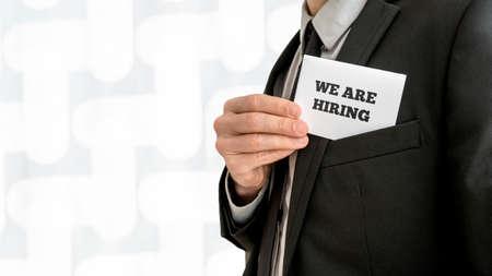 흰색 카드를 제거하는 비즈니스 리더의 근접 촬영 우리는 그의 양복 재킷의 주머니에서 기호를 고용하고있다. 고용과 인적 자원의 개념.