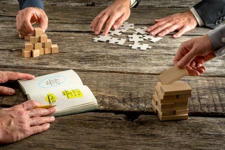 Quattro uomini d'affari brainstorming alla ricerca di idee innovative come uno di loro sta scrivendo calcoli e gli altri tre assemblaggio e costruzione con spine di legno, cubi e pezzi di puzzle. Archivio Fotografico - 47667688