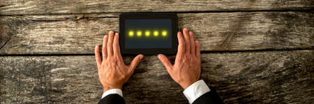 Top view of male hand holding digital tablet with five golden stars appearing on the screen. Conceptual of service and product ranking.