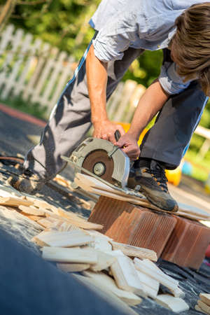 circular: Young man working in his back yard using circular saw to cut wooden planks in order to build a fence around his property. Stock Photo