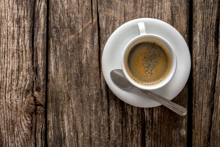 brewed: Top view of delicious hot freshly served cup of black Arabic coffee on a textured rustic wooden desk. Wit copy space on the left side. Stock Photo
