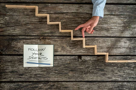 dream: Hand walking his fingers up wooden steps resembling a staircase mounted in rustic boards with a Follow your dreams message. Concept of personal growth and pursuit of ones aspirations and ambitions. Stock Photo
