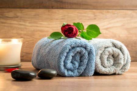 spoiling: Romantic arrangement of two rolled towels with a beautiful red rose on top, lit candle and two black massage stones on a wooden surface. Conceptual of massage, spa and wellness.