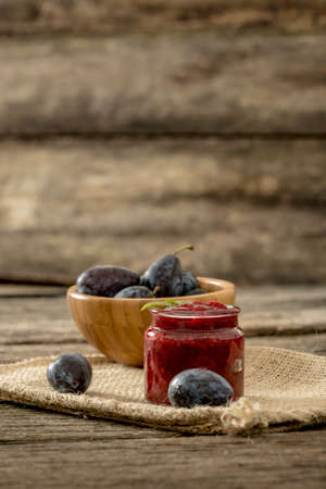 sac: Home made plum marmalade served in a glass jar placed on a burlap sac along wit wooden bowl full of fresh ripe plums. Stock Photo