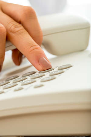 personal call: Closeup of female hand dialing a telephone number on a white landline phone. Conceptual of communication, customer service and personal call. Stock Photo