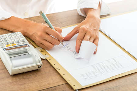 data sheet: Female accountant calculating and reviewing numbers on a receipt as she crosses out numbers that do not match, with statistical report and adding machine on her desk.