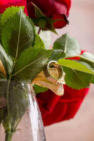 propose: Closeup of engagement ring hanging from a leaf of red blooming rose. Conceptual of love, romance and commitment.