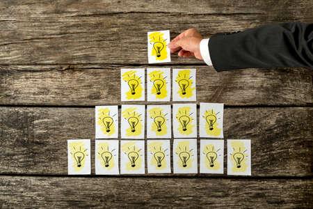 schöpfung: Obenliegende Ansicht der männlichen Hand platzieren weißen Karten mit gelben Glühbirnen in Form einer Pyramide mit der Spitze einer glänzenden das hellste. Konzeptionelle für Innovation, Entwicklung und Vision.