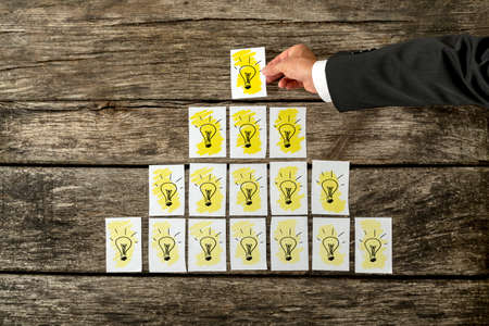 Overhead view of male hand placing white cards with yellow light bulbs in a form of a pyramid with the top one shining the brightest. Conceptual of innovation, development and vision.