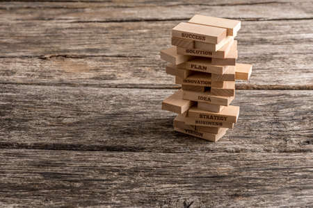 Wooden pegs build in a tower with some of them reading words that represent the most important elements in the way towards success in business - vision, strategy, idea, innovation, plan and solution. Stock Photo