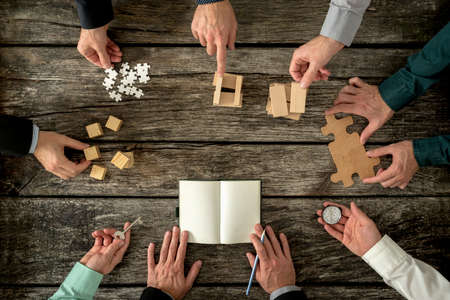 Eight businessmen planning a strategy in business advancement each holding  different but equally important metaphorical element - compass,  puzzle pieces, pegs, cubes, key and one making notes. Archivio Fotografico